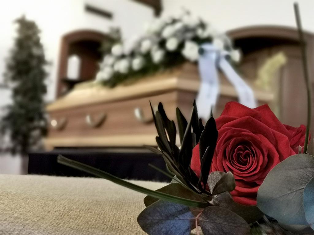 Trauerfeier mit Rose im Vordergrund