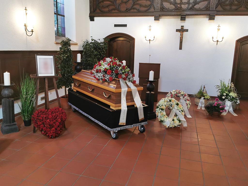 Trauerfeier mit Sarg und weißen und roten Rosengesteck