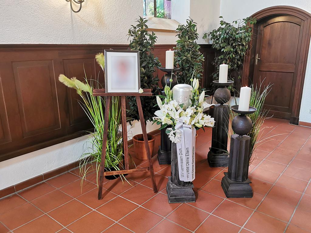 Trauerfeier Urne mit weißen Rosen