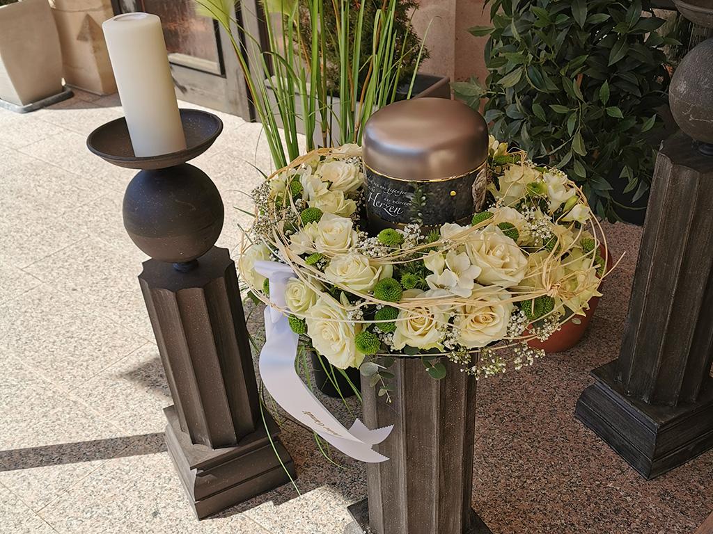 Urne bei Trauerfeier im weißen Blumenkranz von End und Blank Bestattungen
